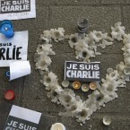 A heart formed by melted candles is on the ground of the Old-Port to pay tribute to the victims of the satirical newspaper