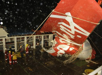 Crew members of Crest Onyx ship unload the wreckage of part of the ill-fated AirAsia Flight 8501 that crashed in the Java Sea