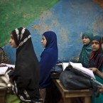 Afghan refugee schoolgirls attend a class at a makeshift school on the outskirts of Islamabad, Pakistan.<span class=