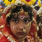 A young Hindu girl sits for a ceremony where she and other girls are worshipped as