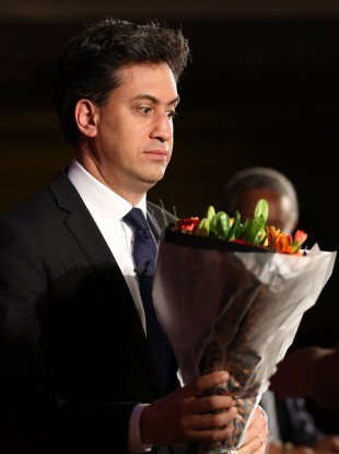 Ed Miliband appears slightly afraid of some flowers he received at an event in London on Monday
