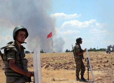 Turkish soldiers stand guard on the Turkish side of the border in Suruc. Kurdish fighters have besieged Islamic State members who entered Kobani.