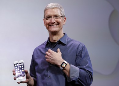 Apple CEO Tim Cook with the iPhone 6 and Apple Watch this time last year.