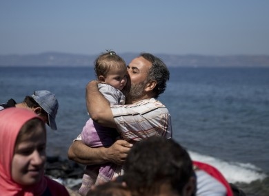 A Syrian man kisses his daughter after they arrived aboard a dinghy from Turkey, to the island of Lesbos, Greece.