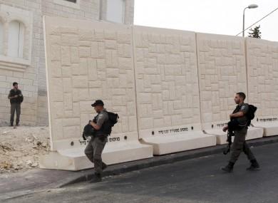 Israeli border policemen walk by the wall being built between Palestinian and Jewish neighbourhoods in Jerusalem.
