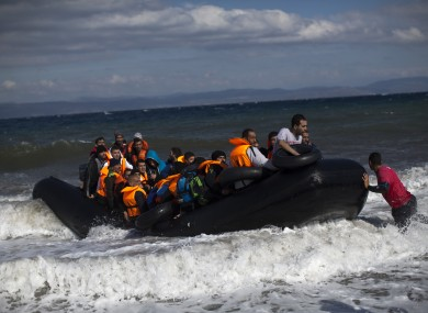 File photo of a rubber boat carrying migrants and refugees arrives at a beach on the northern coast of Lesbos.
