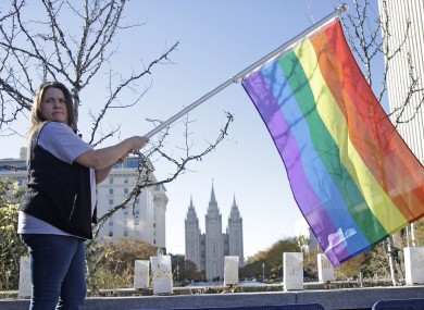 A woman posing with a rainbow flag prior to a mass resignation from the Mormon church last Saturday