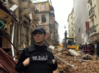 A police officer stands near the collapsed building as firefighters investigate.