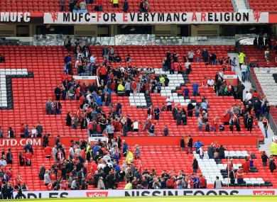 Manchester United fans leave the stand after a security announcement yesterday.