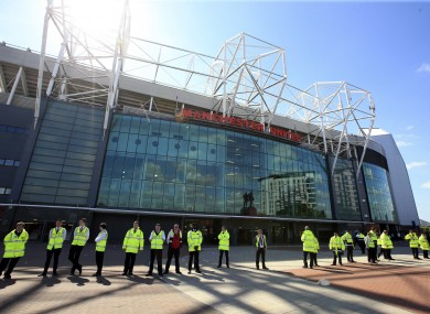 Stewards and police officers stand outside Old Trafford.