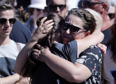 Women react near the scene where a truck mowed through revelers in Nice, southern France, Friday, July 15, 2016.