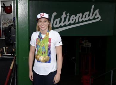 Olympic gold-medal swimmer Katie Ledecky poses with her medals in the dugout before a baseball game between the Baltimore Orioles and the Washington Nationals.