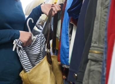 Shoplifter stealing a t-shirt in store.