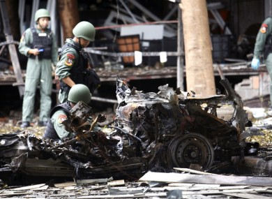 Thai bomb squad officers examine the wreckage of a car after an explosion outside a hotel in Pattani province, southern Thailand.