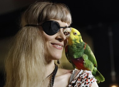 Karen Pease a supporter of the Pirate Party arrives with her parrot named Mal at the Pirate Party election party in Reykjavik, Iceland.