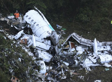 Rescue workers stand at the wreckage site of a chartered airplane that crashed outside Medellin, Colombia.