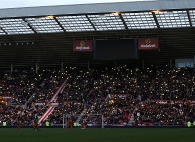 Fans hold their phones up as the stadium lights turn off during the Premier League match at the Stadium of Light.