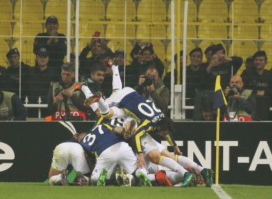 Fenerbahce players celebrate with their teammate Jeremain Lens, obscured, after he scored against Manchester United