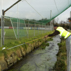 A steward at Clonakilty attempts to retrieve the ball over a stream during the Carbery Rangers-The Nire warm up.<span class=