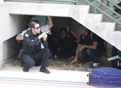 Law enforcement personnel shield civilians outside a garage area at Fort Lauderdale.