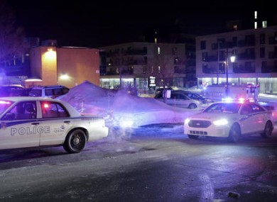 Police survey the scene following the shooting in Quebec City, Canada.