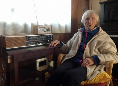 98-year-old Judith Haaland sits next to her decades-old radio set in Stavanger, Norway.