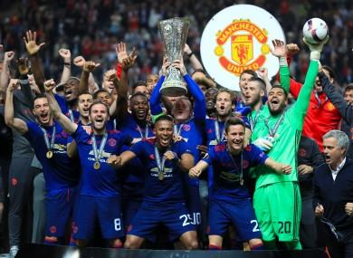 Wayne Rooney lifts the trophy alongside his team-mates.