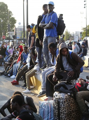 Migrants waiting to be removed from aid centre in Paris.