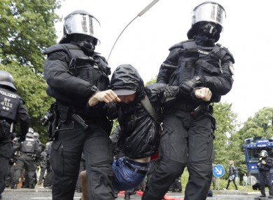 Police officers carry a demonstrator who blocked a street on the first day of the G-20 summit in Hamburg, northern Germany.
