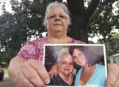 Susan Bro holds up a photo of her daughter Heather Heyer pictured with Susan's mother.