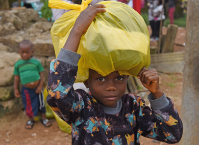 A boy gets free clothes at the Saio Elementary Community School after the mudslides in Freetown