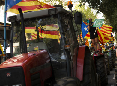 A woman with the estelada, or Catalonia independence flags, shouts slogans on top of parked tractors during a protest by farmers in Barcelona today.