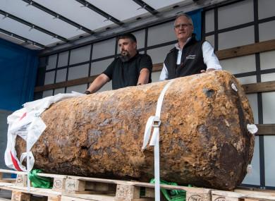 Bomb disposal experts showcasing the hefty British bomb afterwards