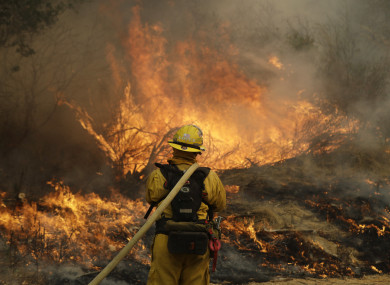 Fresno firefighter Peter Lopez holds a water hose as he monitors a backburn while fighting a wildfire.