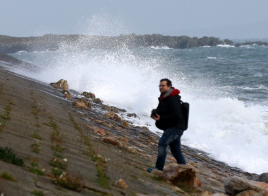 A man walking on Howth Harbour as large waves as Ex-Hurricane Ophelia battered Ireland