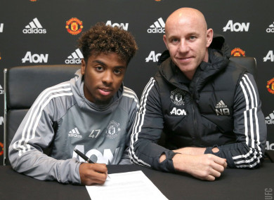 Gomes signs with United's head of academy Nicky Butt.