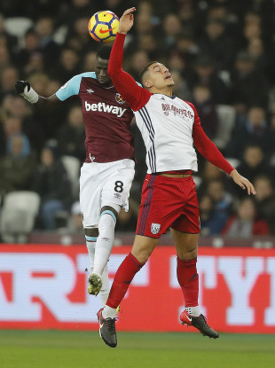 West Brom's Jake Livermore challenging for a header with West Ham's Cheikhou Kouyate.
