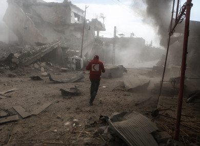 A Syrian Red Crescent volunteer inspects a site that was targeted by rockets fired by warplanes of the Syrian government in the rebel-held town of Douma, Eastern Ghouta.