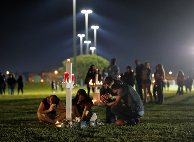 People sitting during a candlelit vigil for the victims of the shooting.