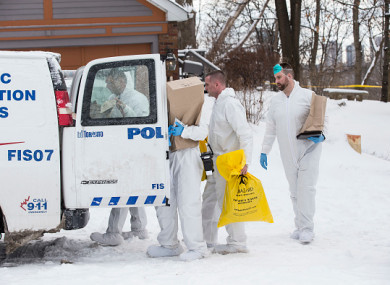 Forensic investigators remove evidence from inside a home in Toronto.