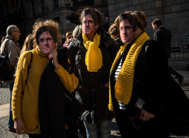 Women wearing cut-out masks of the former Catalan President, Carles Puigdemont pose for a picture, 30 January 2018.