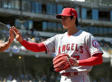 Shohei Ohtani #17 of the Los Angeles Angels high fives with a team mate.