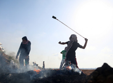Palestinian demonstrators throw stones at Israeli soldiers near the fence during a protest on the Gaza Strip border with Israel.