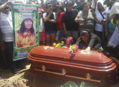 People cry over the coffin of plant healer Olivia Arevalo during her burial in Ucayali, Peru.