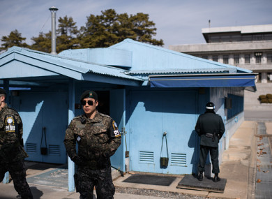 South Korean soldiers stand guard before the military demarcation line and North Korea's Panmun Hall, in the truce village of Panmunjom.