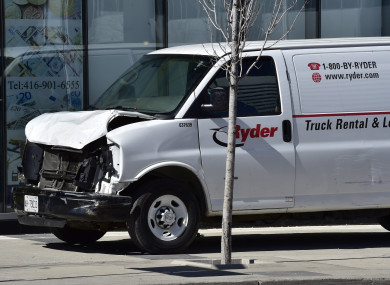 A van with a damaged front-end is shown on a sidewalk after a van mounted a sidewalk crashing into a number of pedestrians.