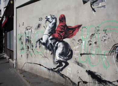 A graffiti piece believed to be attributed to street artist Banksy is seen on a wall along a street in Paris.