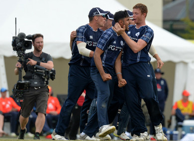 Safyaan Sharif is mobbed by his team mates after taking the final wicket of the game.