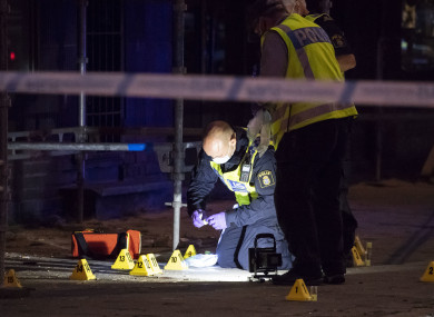 Police forensics investigate the scene after people were shot and injured outside an Internet Cafe in Malmo.