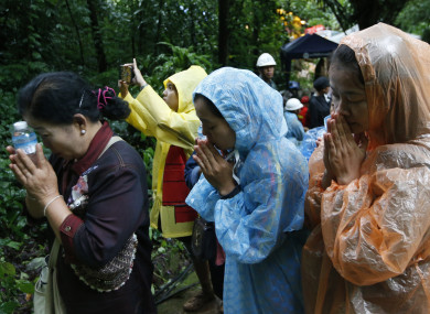 Relatives pray for the return of their loved ones near the site.